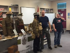 Guest Speakers Dean Fraser (Former Canadian Soldier & UN Peacekeeper (Bosnia) and Mark Ivans War Historian and BC Sheriff, present to LSS students in the library. Here, they have dressed up an LSS student in authentic clothing and gear.